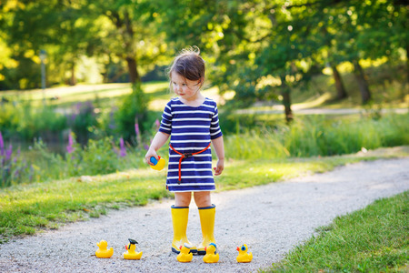 Beautiful little girl of 2 in rain boots playing with yellow rubber ducks in summer park. photo