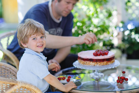 Little boy and his father eating cherry cake photo