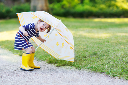 rain boots: Adorable little toddler girl having fun with umbrella in yellow rain boots and umbrella in summer park. Stock Photo