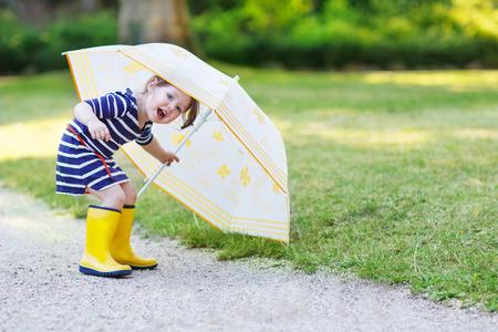 botas de lluvia: Ni�a adorable del ni�o que se divierte con el paraguas en botas de lluvia amarillos y paraguas en el parque de verano. Foto de archivo