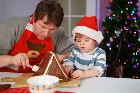 Father and toddler boy preparing a gingerbread cookie house at christmas time photo