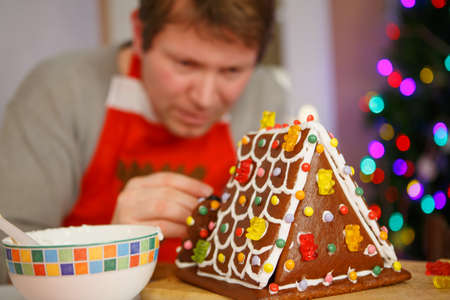 Young man preparing a gingerbread cookie house for his children at christmas time. Selective focus on house photo