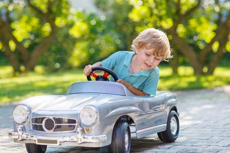 Happy kleine jongen rijden grote speelgoed auto en plezier, buitenshuis.