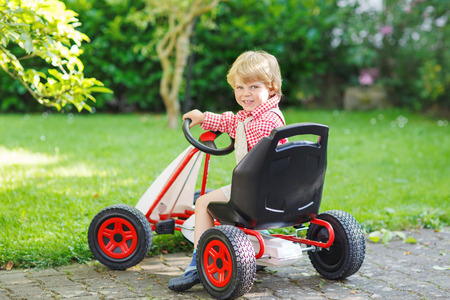 Active little boy of 3 years driving pedal car in summer garden, outdoors. photo