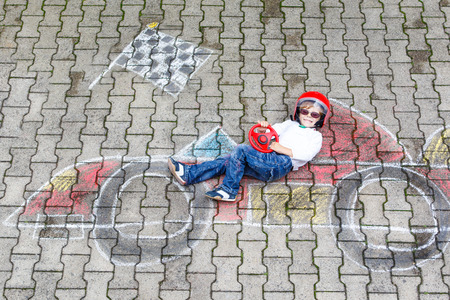 racecourse: Creative leisure for children: Happy little child of four years having fun with race care picture drawing with chalk.