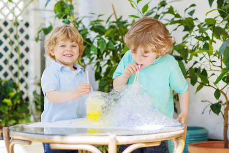Two happy children making experiment with colorful soap bubbles and water, outdoors. photo