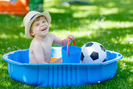 kiddie: Little toddler child in hat having fun with splashing water in summer garden pool