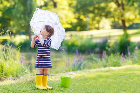 Adorable little toddler girl in yellow rain boots and umbrella in summer park.