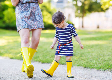 Mother and little adorable daughter in yellow rubber boots, family look, playing with duck toys in summer park photo