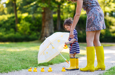Mother and little adorable child girl in yellow rubber boots playing with umbrella, family look, in summer park 版權商用圖片