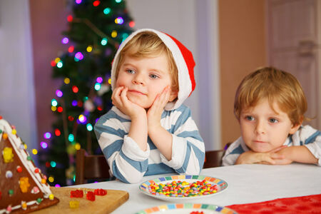 Two little siblings boys happy aboutn selfmade gingerbread cookie house at christmas time. Selective focus on one child photo