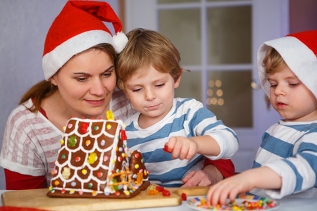 Mother and her two little sons preparing a gingerbread cookie house at christmas time photo