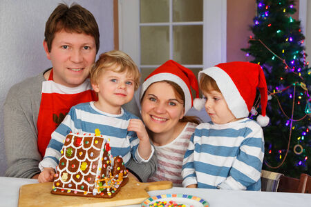 Happy family of four: Father, mother and two little sons with selfmade gingerbread cookie house at christmas time photo