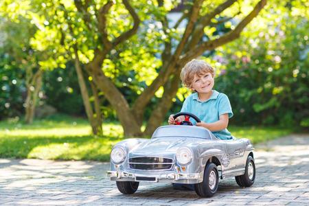 brinquedo: Rapaz pequeno que conduz grande carro de brinquedo e se divertindo, ao ar livre.