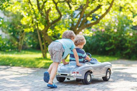 야외, 여름 정원에서 큰 오래된 장난감 자동차를 가지고 노는 두 행복한 아이들.