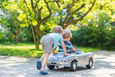 Two happy children playing with big old toy car in summer garden, outdoors.