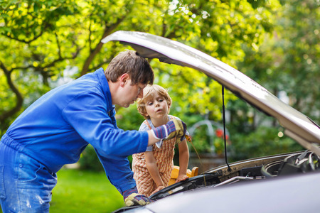engine oil: Young father teaching his little son to change motor oil in family car. Stock Photo