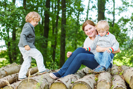 Young mother and her two little children having fun in summer forest photo