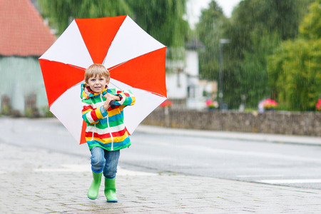Funny boy having fun with red umbrella, wearing colorful raincoat and green boots outdoors at rainy day