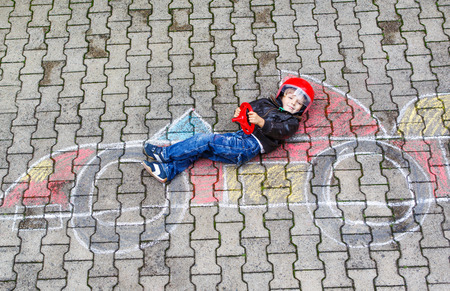 having fun: Creative leisure for children: Funny little boy having fun with race care picture drawing with chalk.