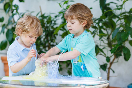 Two adorable preschool boys playing, having fun and making experiment with colorful soap bubbles and water, outdoors. photo