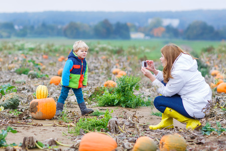 pumpkin patch: Young mother making picture on mobile phone of her child on pumpkin patch
