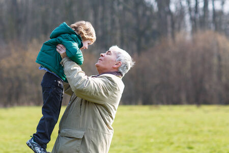 grandfather and grandson: Happy grandfather and his little grandson having fun together outdoors