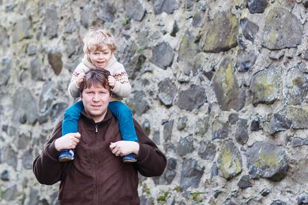 kinship: Happy little boy sitting on fathers shoulders