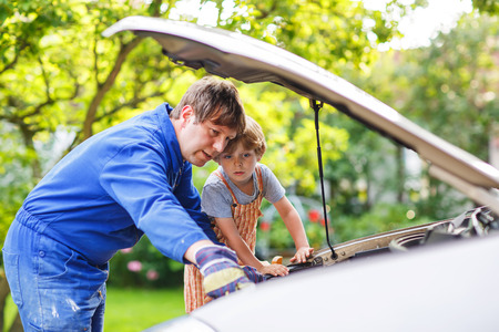 Young father teaching his little son to change motor oil in family car. photo