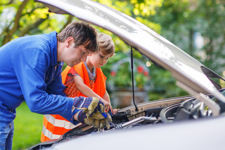 Young father teaching his little son in safety vest  to repair motor oil in family car.