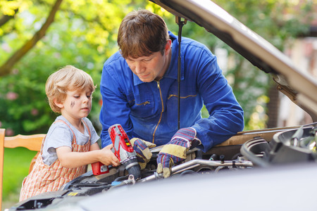 Young father teaching his little boy to repair motor oil in family car. photo