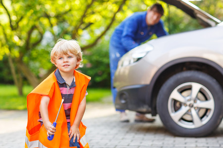Little boy in orange safety vest during his father repairing family car on background photo