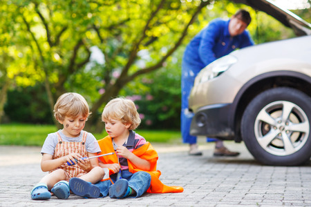 Two little sibling boys in orange safety vest during their father repairing family car on background photo