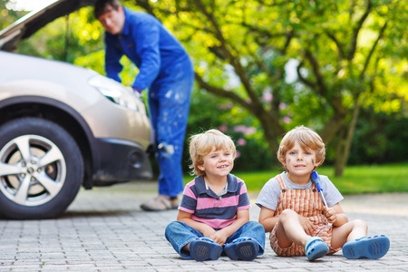 Two little sibling boys during their dad repairing family car on background photo