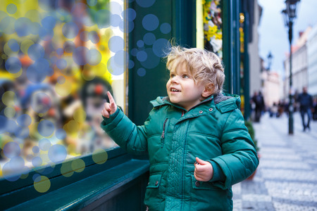 window display: Adorable little boy looking through the display window at Christmas decoration in the shop
