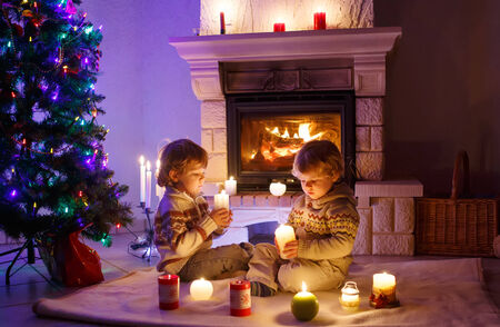 fireplace family: Two little happy boys sitting by a fireplace at home on Christmas time Stock Photo