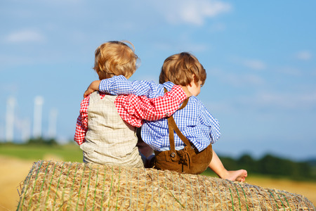 Two little children and friends sitting on hay stack or bale and speaking on yellow wheat field in summer