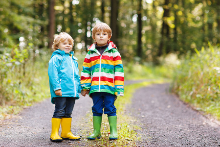 Two little children in colorful waterproof raincoats and rubber boots walking through autumn forest together.