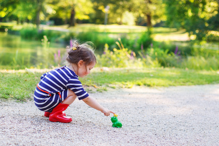 Adorable little toddler girl in red rain boots playing with rubber toy frog. Outdoors. Fairytale concept photo