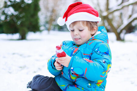 Happy little toddler boy with chocolate Santa waiting for Christmas santa hat, sitting on snow in winter garden, outdoors. photo