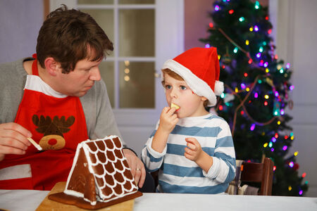 Dad and his little son having fun with baking a gingerbread cookie house at christmas time, homes kitchen photo