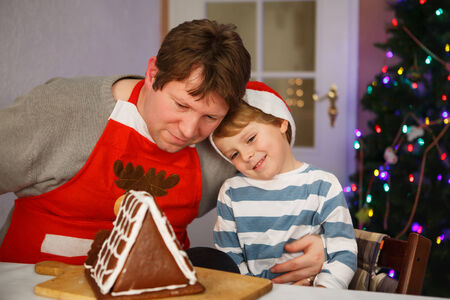 Dad and his little adorable child having fun with baking a gingerbread cookie house at christmas time, homes kitchen photo