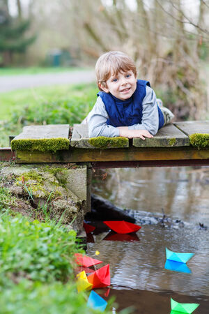 Adorable little kid boy playing with colorful paper boats by a river on spring or autumn day. Creative leisure with kids. Reklamní fotografie
