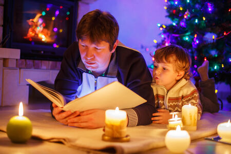 Young father and his little child reading book by a fireplace on Christmas photo