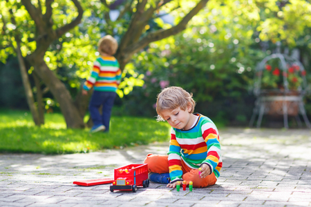 Little child playing with red school bus and toys in summer garden. photo