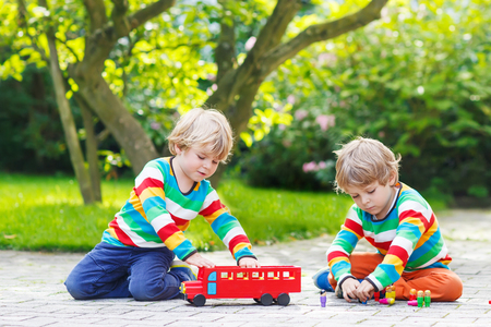 Two twin boys in colorful clothing with stripes playing with red school bus and toys in summer garden on warm sunny day. Learning to play and communicate together. photo