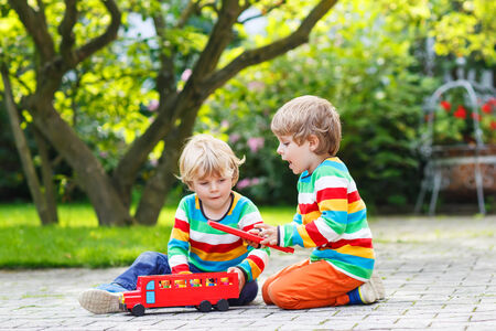 Two little children in colorful clothing with stripes playing with red school bus and toys in summer garden on warm sunny day. photo