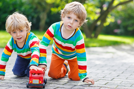 Two little siblings, kid boys in colorful clothing with stripes playing with red school bus toy in summer garden on warm sunny day. photo