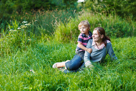 Little boy and his mother having fun together in nature landscape photo