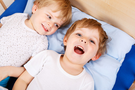 Two Little Toddler Boys Having Fun In Bed Before Sleeping Photo